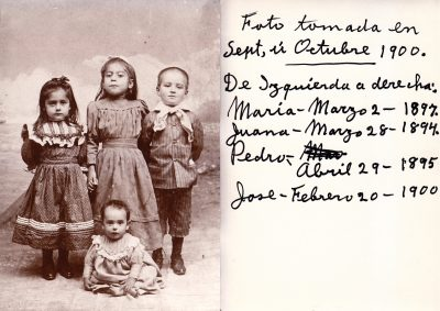 4 children in a vintage sepia toned photograph. Jose Guerrero Perez is 8 months old and is sitting on the ground in the center.
