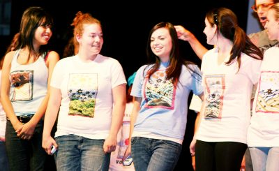Students on stage in the CSULB University Theater wearing Hildegard von Bingen t-shirts of their own design