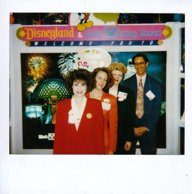 4 Disney Employees stand in a line at the Disneyland / Walt Disney World booth at the Radio-Television News Director's Association annual conference. Jennifer in a red suit, Barbara in an orange suit, Johanna in a green suit, and Glenn in a blue suit