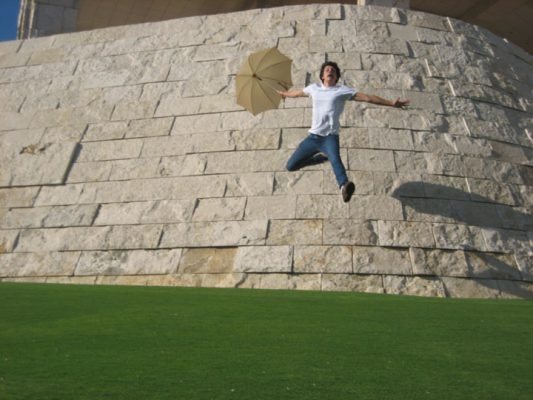 Ryan Ford with an umbrella seeming to fly off a wall at The Getty Center in Westwood