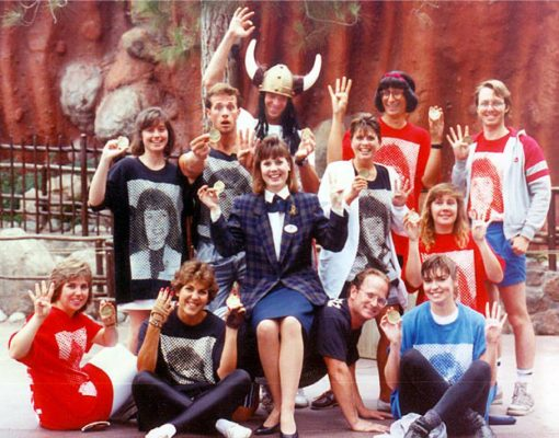 "Disneyland Entertainment Art Department, ""DEAD"" 1989 Canoe Team posing for a photo. Wendy Freeland, Disneyland Ambassador to the World sits in the middle. Everyone else wears t-shirts with giant halftone dot photos of Wendy in red, blue, or black"